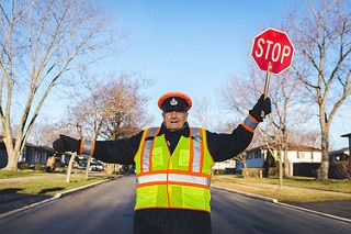 crossing guard holding up a stop sign, crossing guard, austin isd, austin school district, austin schools, austin school schedules, round rock isd, hays consolidated isd, leander isd