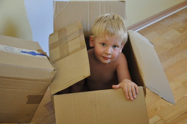 small boy peeking out of a moving box, moving with kids, moving with children, top austin realtor