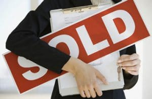 realtor holding paperwork and a large sold sign, sold, get your home ready to sell, sell your home, sherri williams, sherri williams realtor, keller williams realty, top austin realtors